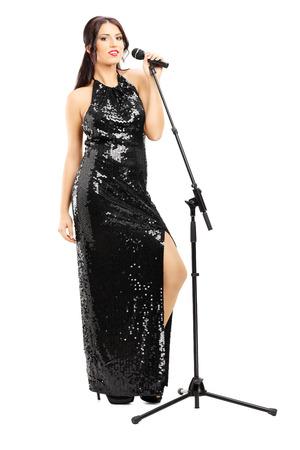 黒いドレスの白で隔離されるポージングで若い女性歌手の完全な長さの肖像画