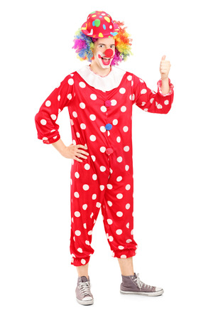 Full length portrait of a smiling happy clown in red costume giving thumb up isolated on white background photo