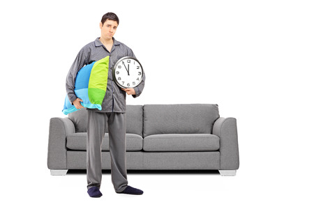 Full length portrait of young sleepy guy holding a wall clock and pillow, with modern sofa in the background Stock Photo - 24594063