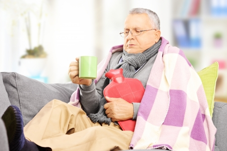 grippe: Ill middle aged man on a sofa covered with blanket drinking hot tea at home
