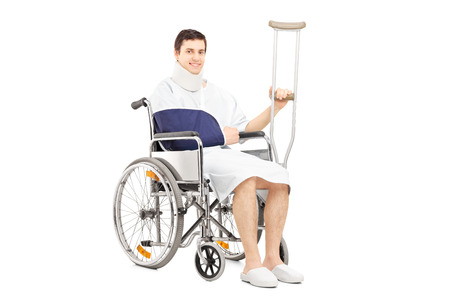 arm chairs: Smiling male patient with broken arm in a wheelchair holding a crutch isolated on white background