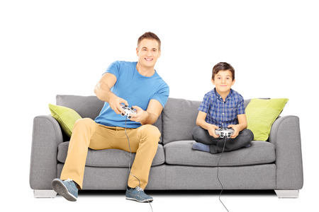 kids playing video games: Two brothers seated on a sofa playing video games isolated on white background