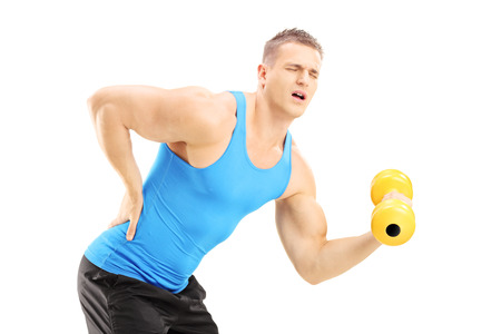 muscle injury: Young male athlete with back pain lifting a dumbbell isolated on white background