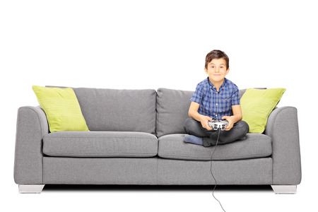 kids playing video games: Young smiling kid seated on a sofa playing video games isolated on white background