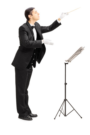 Full length portrait of a male orchestra conductor directing with stick isolated against white background photo