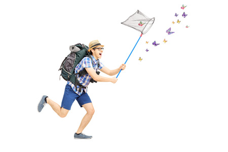 Full length portrait of a male tourist catching butterflies with net isolated on white background photo