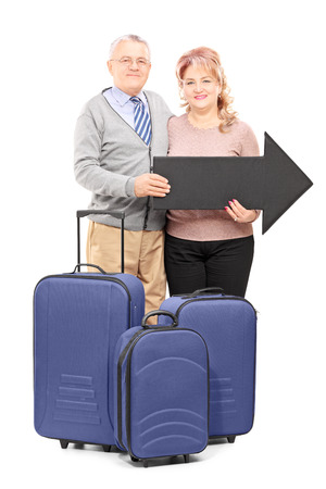 60s adult: Full length portrait of a smiling mature tourists holding a big black arrow and travel bags isolated on white background