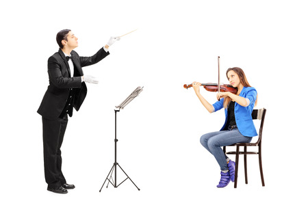 Male orchestra conductor directing a female playing violin isolated against white background photo