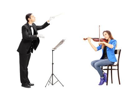 Man dirigent leiding geven aan een vrouwelijke spelen viool geà ¯ soleerd tegen een witte achtergrond