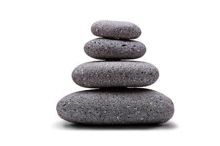steadiness: Stack of balanced stones isolated on white background
