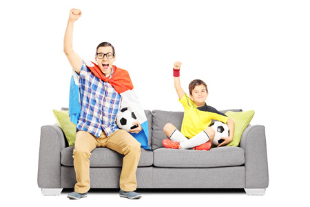 Two male sport fans seated on a sofa watching sport isolated on white background