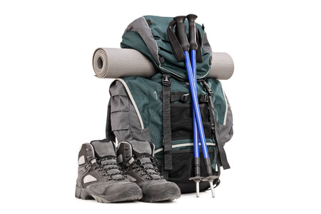 Hiking equipment, rucksack, boots, poles and slipping pad isolated on white background Stock Photo