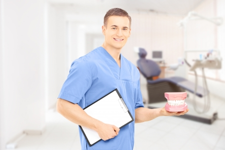Male dentist surgeon holding dentures and clipboard at his workplace Stock Photo - 24594125