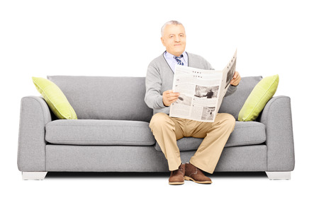 reader: Senior gentleman sitting on a modern sofa with newspaper looking at camera isolated against white background Stock Photo