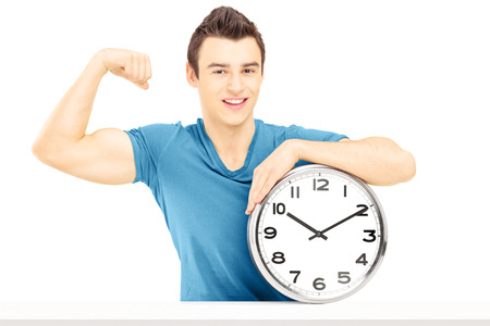 Young smiling man seated on a table with wall clock showing his muscles isolated on white background photo