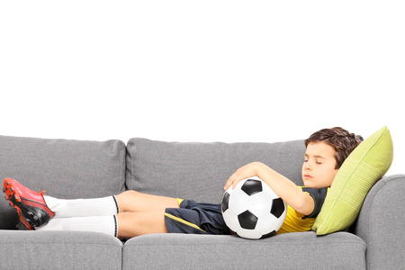 plimsoll: Boy in sportswear with a football sleeping on a modern sofa isolated on white background