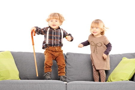 Brother and sister standing and playing on a sofa isolated on white background photo