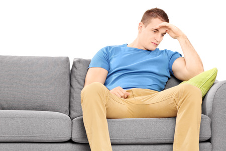 dissappointed: Dissappointed young man sitting on a couch isolated on white background