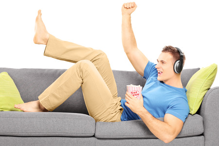 Excited guy lying on a modern couch and listening music isolated on white background Stock Photo - 24594193