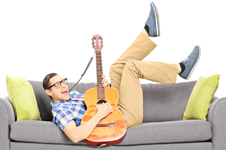 Excited young male lying on a modern couch and playing a guitar isolated on white background photo
