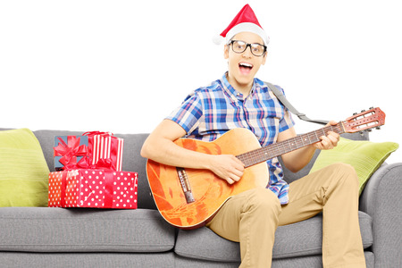 holiday music: Excited young male with christmas hat seated on sofa playing an acoustic guitar isolated on white background Stock Photo