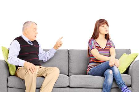 disagreeing: Father reprimending his uninterested daughter seated on a sofa isolated against white background