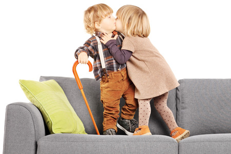 Girl kissing a boy while standing on a  modern sofa isolated on white background photo