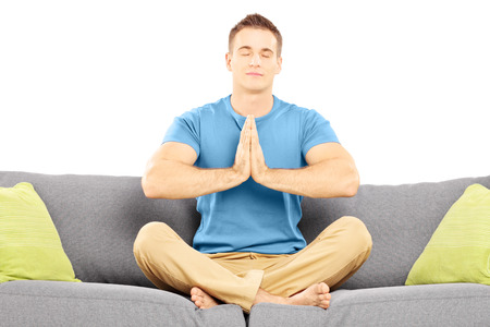 Guy meditating seated on a sofa isolated against white background photo