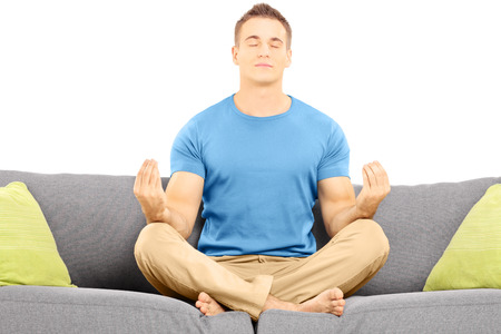 Guy meditating seated on a sofa isolated on white background photo