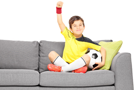 Happy boy in sportswear with a football sitting on a sofa and gesturing happiness isolated on white background Stock Photo - 24594208