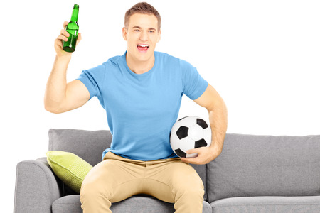 soccer fan: Happy cheerful male sport fan with soccer ball and beer bottle watching sport isolated on white background