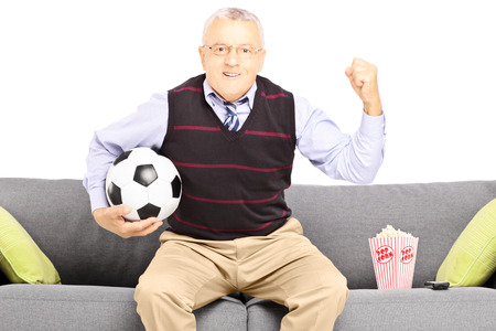 Middle aged sport fan holding a soccer ball and watching sport isolated on white background photo