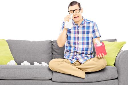 hombre sentado: Chico triste que se sienta en un sofá y secándose los ojos de tanto llorar aisladas sobre fondo blanco Foto de archivo