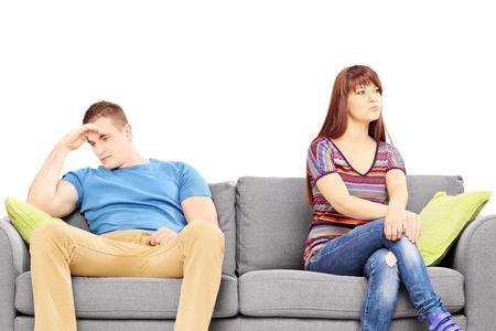 novios enojados: Pareja joven triste que se sienta en un sof� despu�s de una discusi�n aislada en el fondo blanco