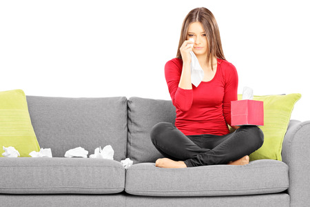 Sad young female sitting on a couch and wiping her eyes from crying isolated on white background Stock Photo