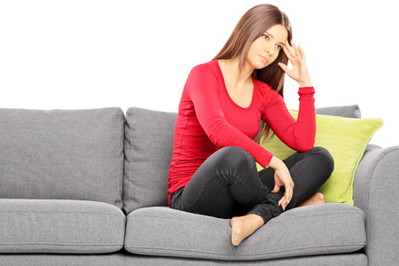 Sad young woman sitting on a modern sofa isolated on white background photo