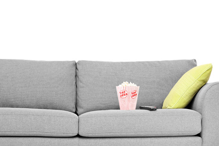 Studio shot of a modern sofa with popcorn box on it isolated on white background photo