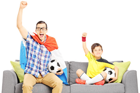 euphoric: Two male sport fans sitting on a sofa and watching sport isolated on white background