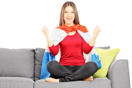 supporter: Young female sport supporter sitting on a modern couch and cheering, isolated on white background Stock Photo