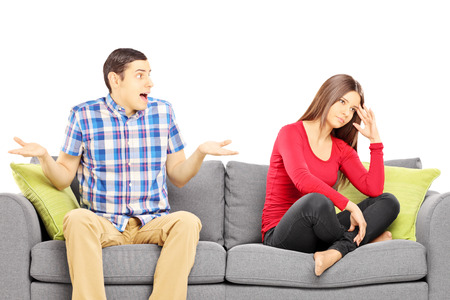 couple arguing: Young heterosexual couple sitting on a sofa during an argument isolated on white background Stock Photo