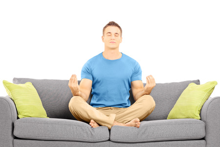 Young male meditating seated on a couch isolated against white background photo