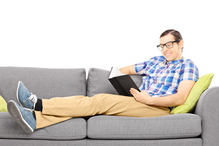 Young male on a couch reading a book isolated on white background photo