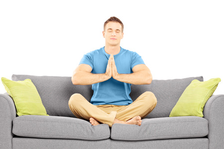 Young man meditating seated on a sofa isolated on white background photo