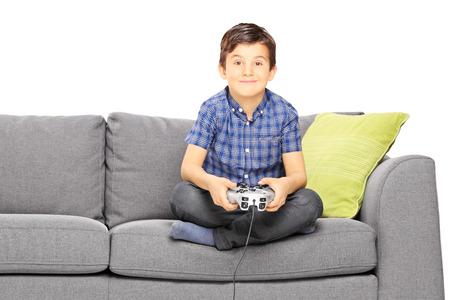 niños jugando videojuegos: Niño sonriente joven sentado en un sofá jugando videojuegos aisladas contra el fondo blanco Foto de archivo