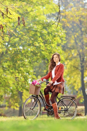 Beautiful female on a bicycle in a park looking at camera photo