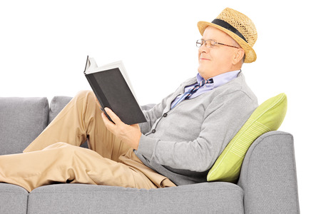 Senior man with hat on a sofa reading a novel isolated on white background photo