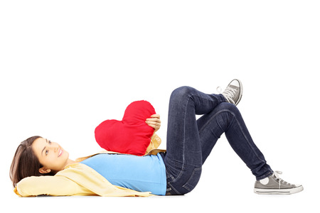 Smiling young female lying down with red heart in her hand isolated on white background photo