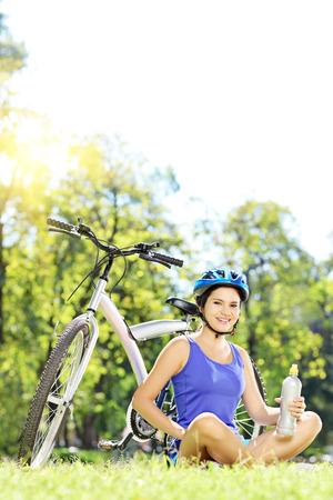 mountain biker: Young female biker with helmet sitting on a grass next to her mountain bike in a park, and relaxing on a sunny day