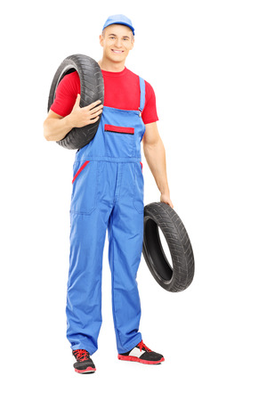 Full length portrait of a male mechanic holding a vehicle tires and looking at camera isolated on white background Stock Photo - 24657263