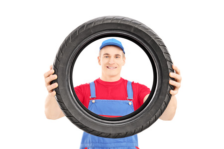 Smiling male worker holding a vehicle tire and looking at camera isolated on white background Stock Photo - 24657268